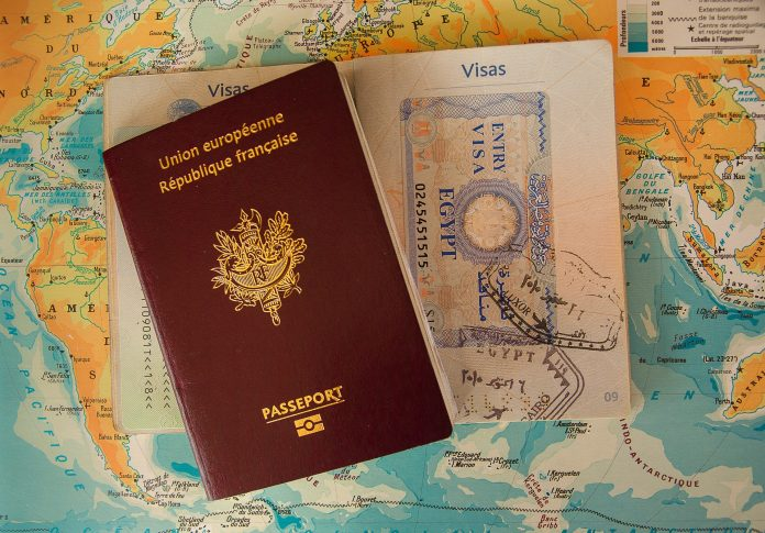 brown passport and visa documents